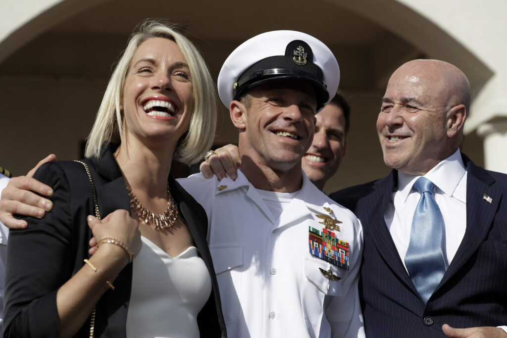 Navy Special Operations Chief Edward Gallagher, center, walks with his wife, Andrea Gallagher, and advisor, Bernard Kerik as they leave the military court on Naval Base San Diego on Tuesday. A military jury acquitted the decorated Navy SEAL of murder in the killing of a wounded Islamic State captive under his care in Iraq in 2017.