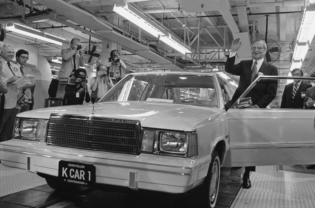 Chrysler Chairman Lee Iacocca steps into the first K-Car at ceremonies in Detroit, Mich., on Aug. 6, 1980. The new front-wheel-drive compact was driven out of the plant past cheering auto workers by Iacocca. Iacocca, who became a folk hero for rescuing the company in the '80s, died Tuesday. He was 94.