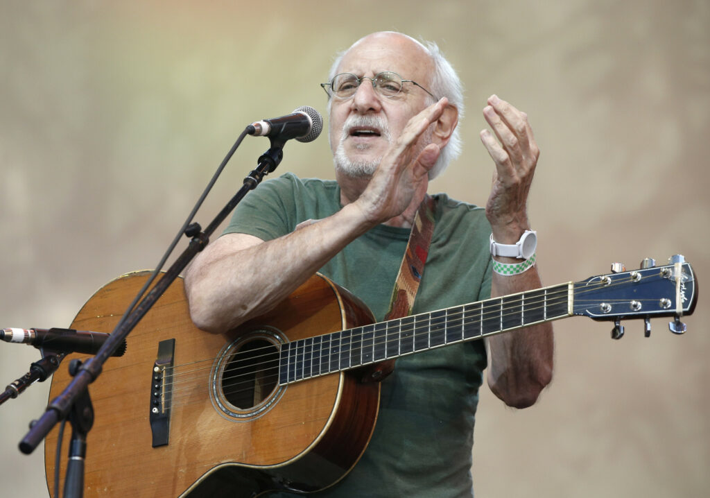 "In this July 20, 2014, file photo, singer-songwriter Peter Yarrow, of the 1960's era musical trio ""Peter Paul and Mary,"" claps and encourages the audience to sing along during a memorial tribute concert for folk icon and civil rights activist Pete Seeger at Lincoln Center's Damrosch Park in New York."