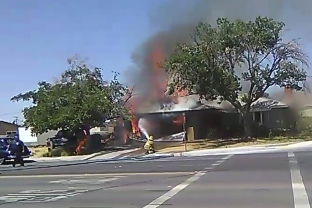 In this image taken from video provided by Ben Hood, a firefighter works to extinguish a fire Thursday after an earthquake in Ridgecrest, Calif.