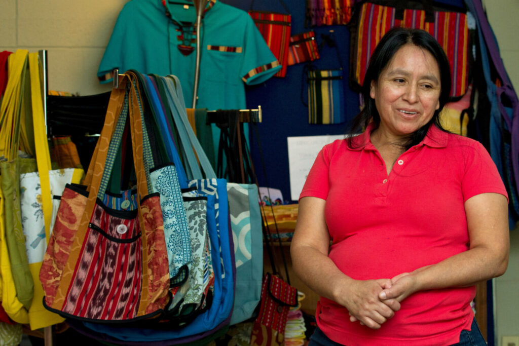 Maria Chavalan-Sut of Guatemala stands next to items she has made at the Wesley Memorial United Methodist Church in Charlottesville, Va. She uses fabric that a son has mailed to her from Guatemala to make a range of goods. She can't sell them, but she accepts donations in exchange.