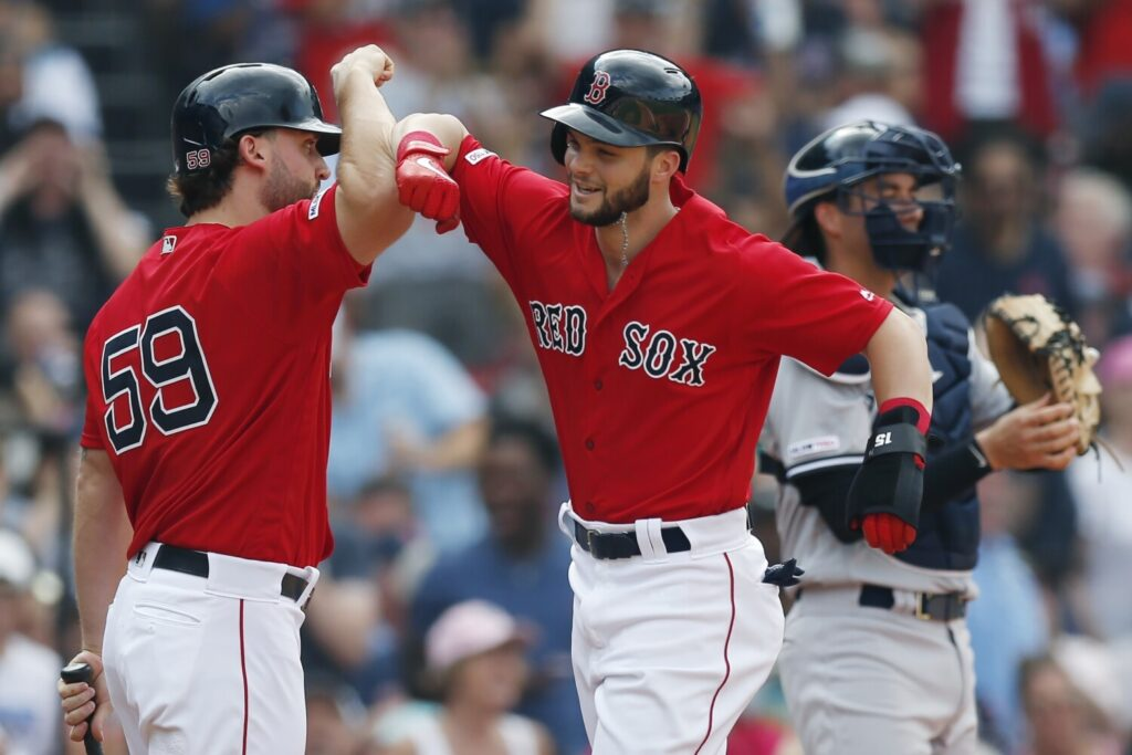 Andrew Benintendi celebrates his solo home run with Sam Travis during the Red Sox game against the New York Yankees on Saturday in Boston.