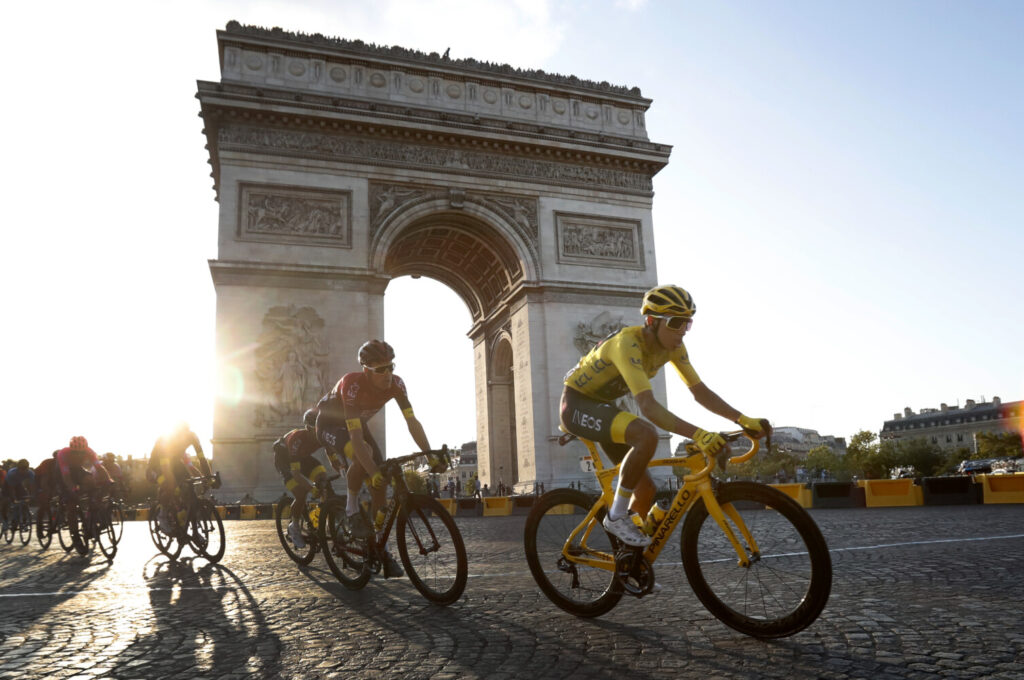 Colombia's Egan Bernal wearing the overall leader's yellow jersey, center, rides past the Arc de Triomphe on the Champs-Elysees during the final stage of the Tour de France on Sunday.
