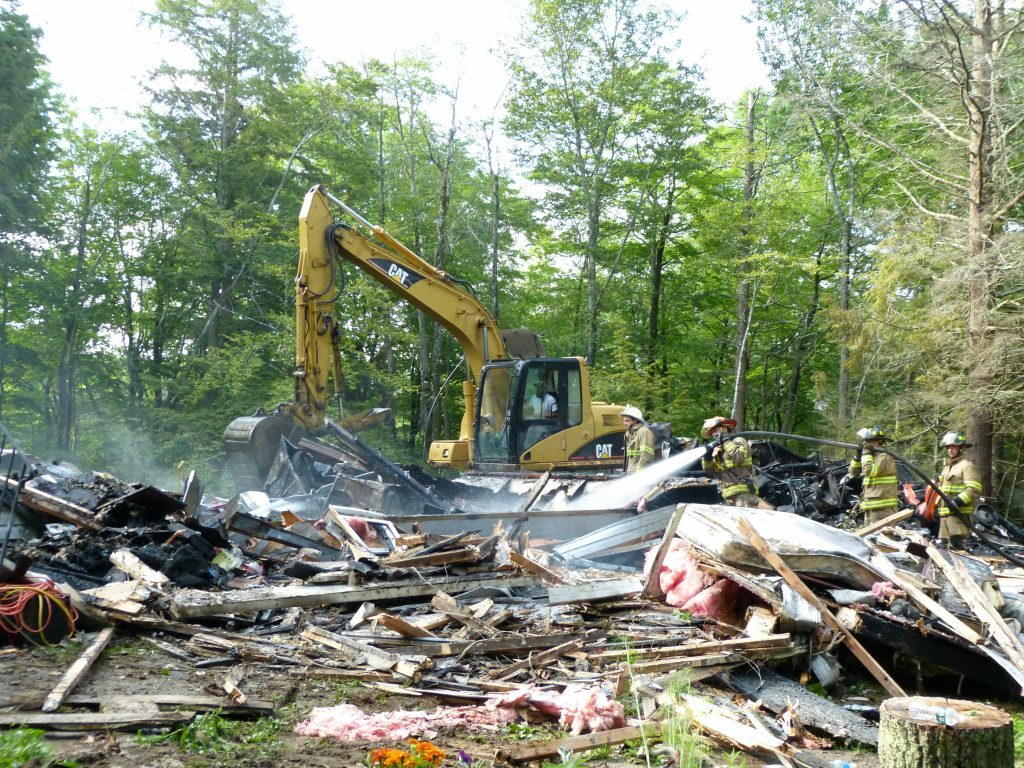 An excavator digs through the remains of a Bowdoinham home destroyed by a fire the morning of June 30 as firefighters hose down smoldering debris.