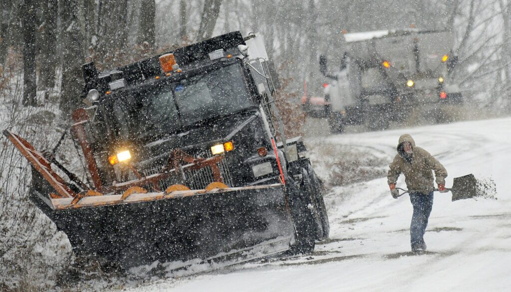 Jake Laughlin tosses sand onto Maple Street in Farmingdale on Dec. 5, 2016, as a colleague prepares to descend the snow covered road with a plow truck.