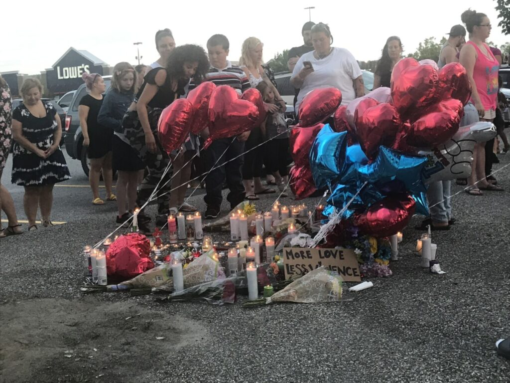 Friends and family members of Jean Fournier, 41, of Turner light candles and set them in a circle Sunday evening during a vigil at the Walmart parking lot in Auburn. Fournier was fatally shot Saturday evening in the parking lot on Mount Auburn Avenue.