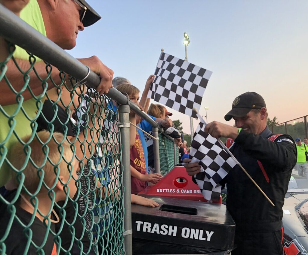 Kevin Douglass of Sidney, far right, signs autographs in victory lane after winning the Pro Stock feature at Wiscasset Speedway on Saturday night in Wiscasset.