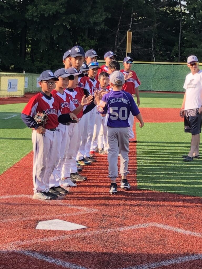 Members of a Chinese youth baseball team greet a Waterville Cal Ripken player prior to an exhibition game Monday at Purnell Field.