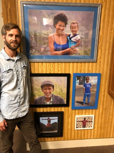 Caleb Baker, of Hallowell, stands on Saturday next to photos he shot during his travels in Cape Verde. The photos were displayed at Post Office Square in Waterville as part of the MIFFONEDGE Volume 7 event.