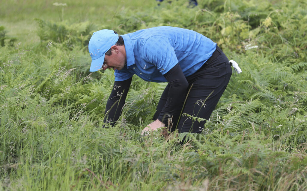 Rory McIlroy looks for his ball in the long rough on the 1st hole during the first round of the British Open on Thursday.