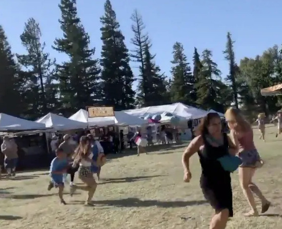 People flee at the Gilroy Garlic Festival on Sunday after reports of a shooter.
