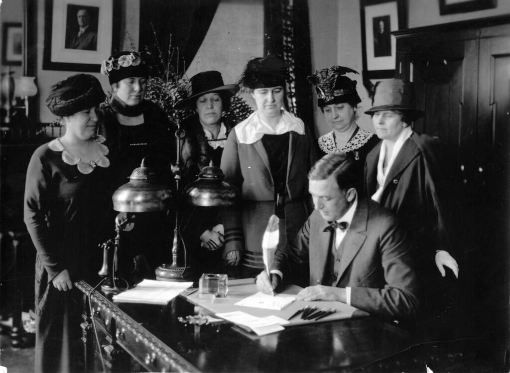 Gov. Carl Millikin signs the ratification of the 19th amendment. From right to left: Florence Brooks Whitehouse, chair, National Women's Party Maine branch; Grace Hill, NWP Maine branch; Mabel Connor, Maine Woman Suffrage Association; Katherine Reed Balentine, MWSA Legislative Committee chairwoman, Gertrude Pattangall, MWSA corresponding secretary, and Anne Gannett, president of the Augusta Woman Suffrage Association.