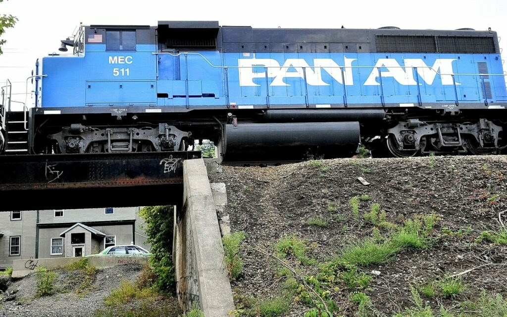 A Pan Am Railways engine pulls railroad cars over a trestle as cars pass below on Front Street in Waterville. The railway and state Department of Transportation are embarking on a $35 million upgrade of the freight line to improve safety and enhance business opportunities, especially with Maine's resurgent paper industry.