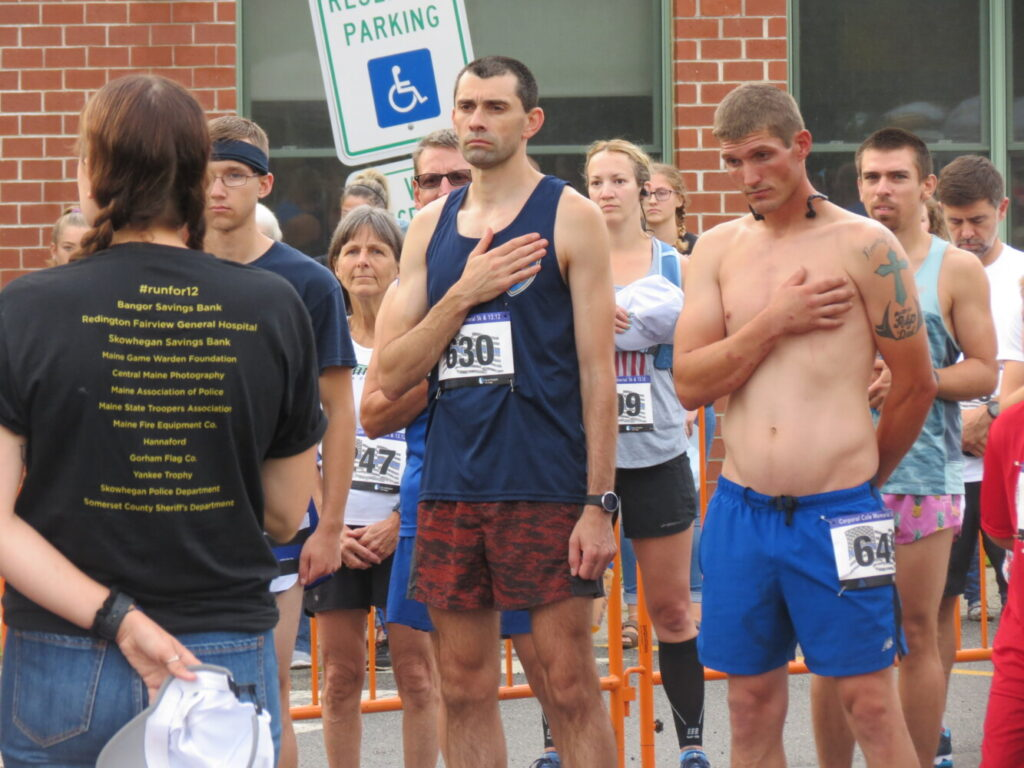 Runners stand for the national anthem prior to Sunday's Corporal Cole Memorial 5K and Half Marathon in Norridgewock.