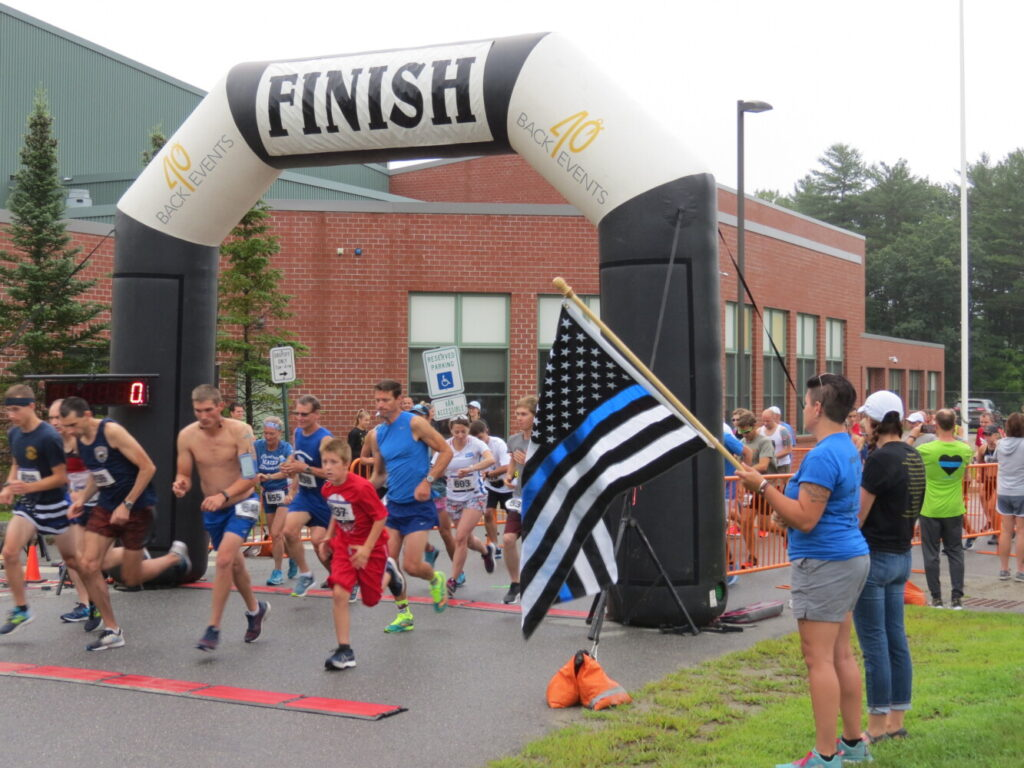 Samantha DeLorie, a planning committee member for the Corporal Cole Memorial 5K and Half Marathon, holds the flag Sunday as runners leave the starting line.
