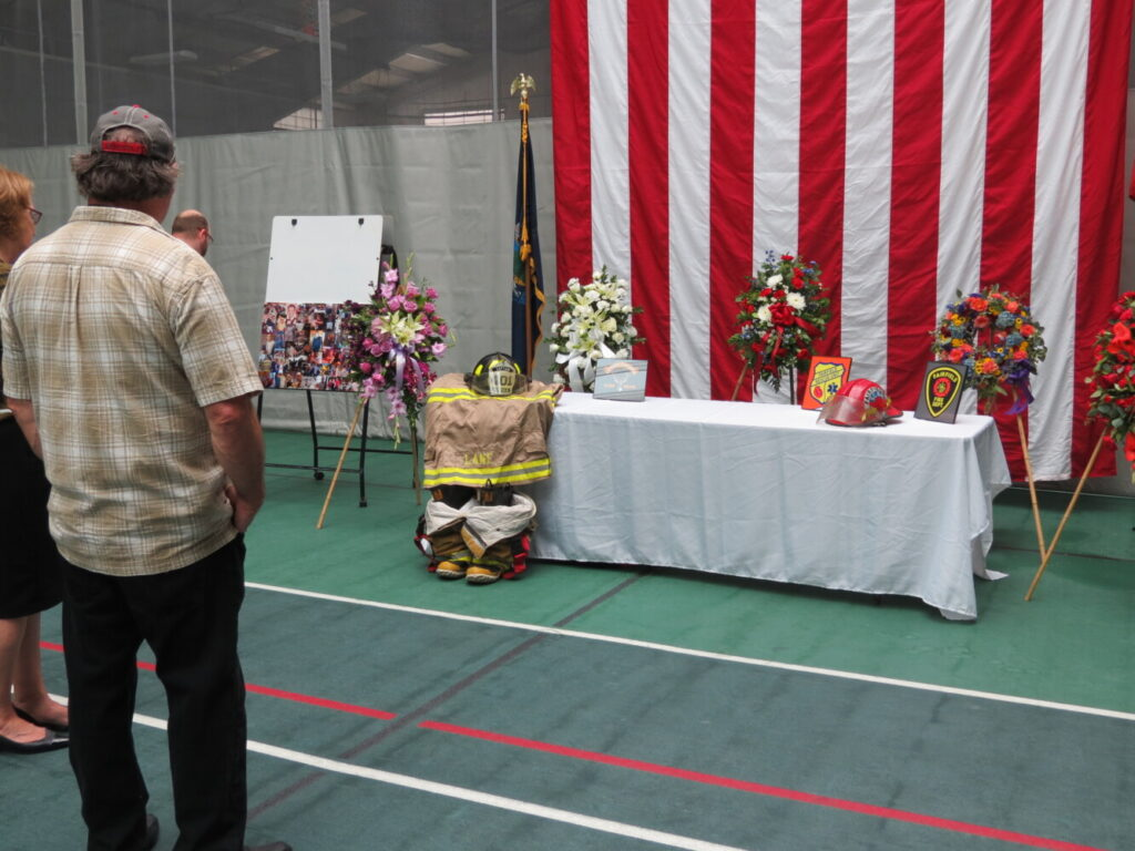 An attendee at Capt. Jim Lane's celebration of life service Sunday looks at the display table with photos of Lane as well as his Fairfield Fire Department uniform.