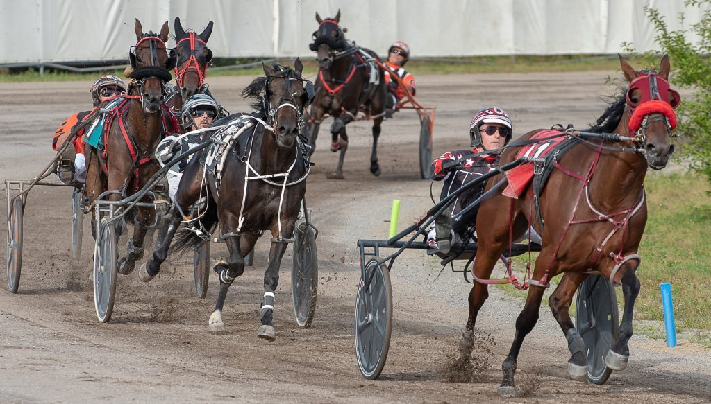 Drivers open up around the final turn during a harness race at the Topsham Fair. (Russ Dillingham /Sun Journal)