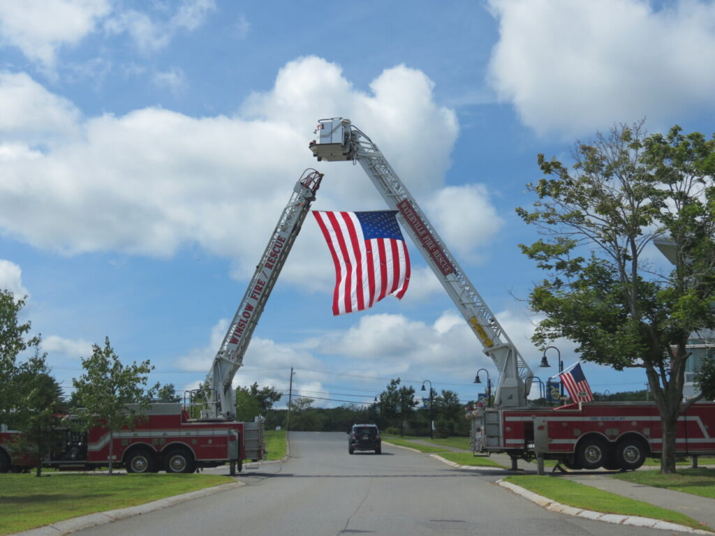 Waterville and Winslow Fire Departments raise a flag at the entrance to Thomas College to honor the late Fire Capt. Jim Lane on Sunday in Waterville.