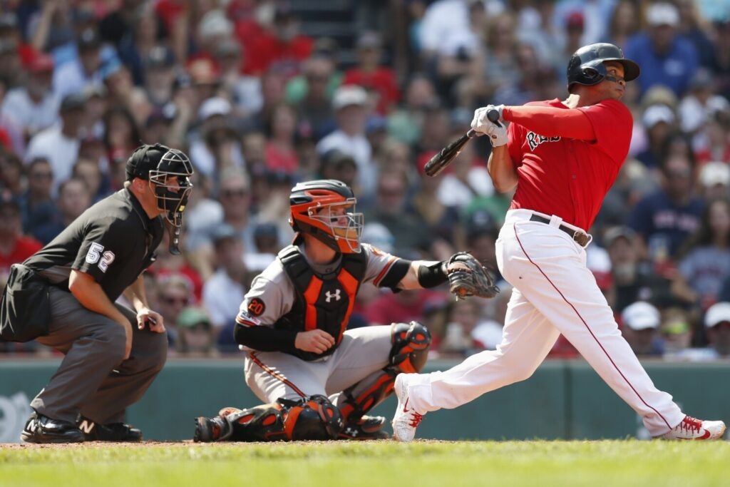 Rafael Devers, right, follows through on an RBI double in the sixth inning of Boston's 13-7 win over Baltimore on Sunday at Fenway Park. Devers had four hits, including two doubles and a home run, and four in four runs.