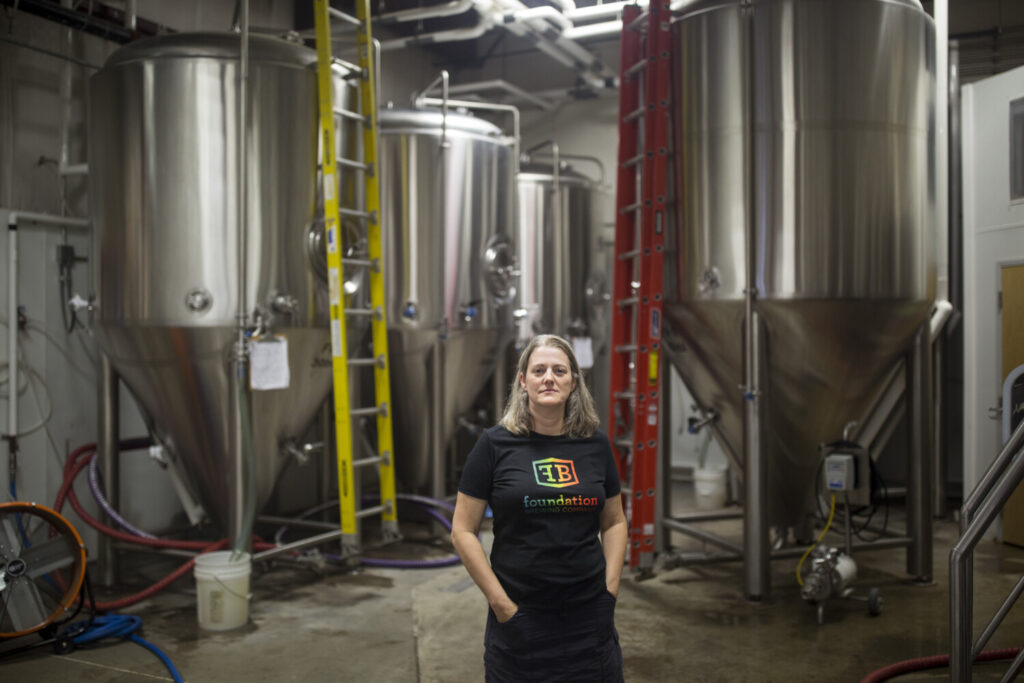 """Tina Bonney, one of the founders of Foundation Brewing, poses for a portrait in their brewing space in Portland. The implementation of a new licensing fee for manufacturing alcoholic beverages caught breweries and wineries in Portland by surprise. """"I'm disappointed we weren't engaged in the process of creating a new ordinance,"""" Bonney said."""