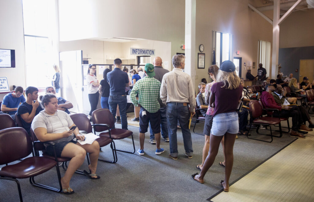 People wait for their numbers to be called at the Bureau of Motor Vehicles in Portland on Aug. 30. The bureau has experienced extra long wait times for many reasons, including an employee shortage.