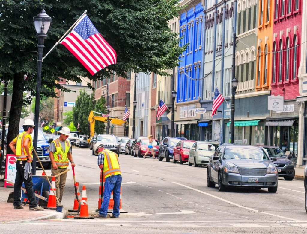 Construction workers tamp down the dirt around a storm drain Tuesday at the corner of Water and Bridge streets in downtown Augusta.