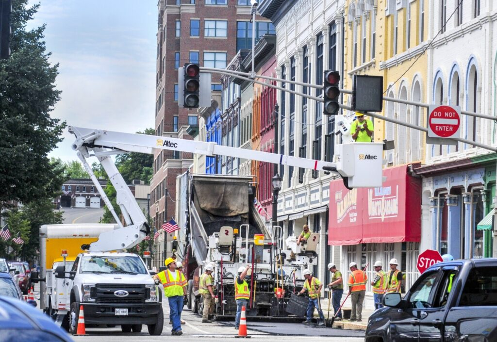 Construction workers pave the road at the corner of Water and Bridge streets Wednesday in downtown Augusta. When the work is completed Monday afternoon, Water Street will be open to two-way traffic.