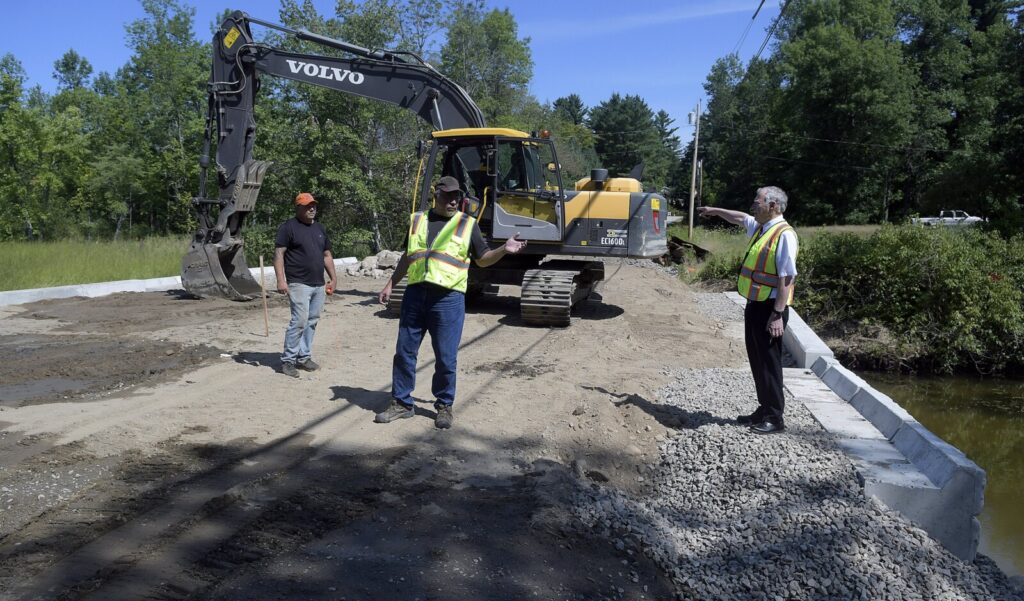 Monmouth Town Manager Curt Lunt, right, speaks Monday with Public Works Director Bruce Balfour, center, and excavator operator Chet Blair on the overpass above the new culvert on the Sanborn Road in Monmouth. The road near the intersection of Route 135 was closed when the culvert backed up in April 2018 and partially collapsed the road. Work on the overpass should be complete by the first week of September, according to contractor P.J. Poirier, who was awarded the $180,000 contract.