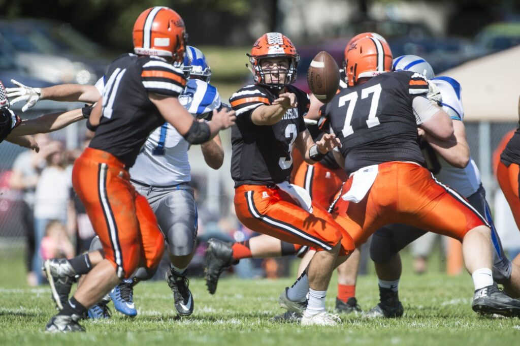 Winslow quarterback Colby Pomeroy (3) pitches the ball to Ben Dorval during a game against Lawrence last season in Winslow. The Black Raiders return 18 letter winners and should be a force in Class C North this fall.