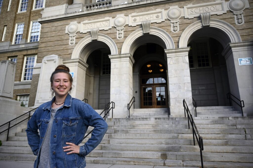 "Meg Baltes, a Portland High School junior, stands in front of the school. ""I think things are handled very swiftly and very aggressively at Portland,"" Baltes said of discipline problems there. More students are choosing to go to Portland High over Deering High this year, partly because of perceived discipline issues at Deering."