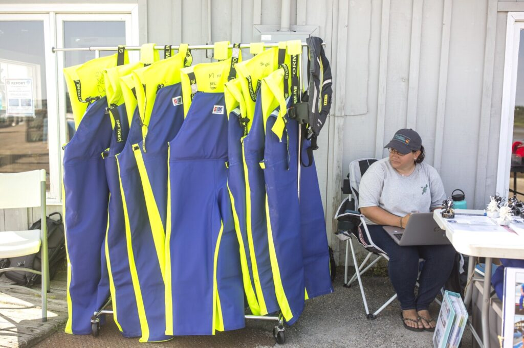 Mandy Roome, a field research coordinator with the Northeast Center for Occupational Health and Safety, sells lifejackets customized for lobstermen on the Cape Porpoise Pier on Thursday. Since April 1, the organization has sold 450 lifejackets, with the coveralls containing flotation devices the most popular option, according to Roome. The group is working its way up the Maine coast, selling a variety of lifejackets at a discount to Maine lobstermen.