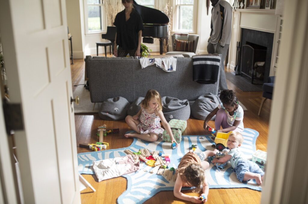 Acacia Kivuvu, 3, right, plays with Levi Rosenberg, 4, left, and Levi's two younger siblings Sawyer and Zaff, while Lauren Rosenberg and Moniz Guenge Pumba, Acacia's father, watch them in the Rosenbergs' living room on Monday.