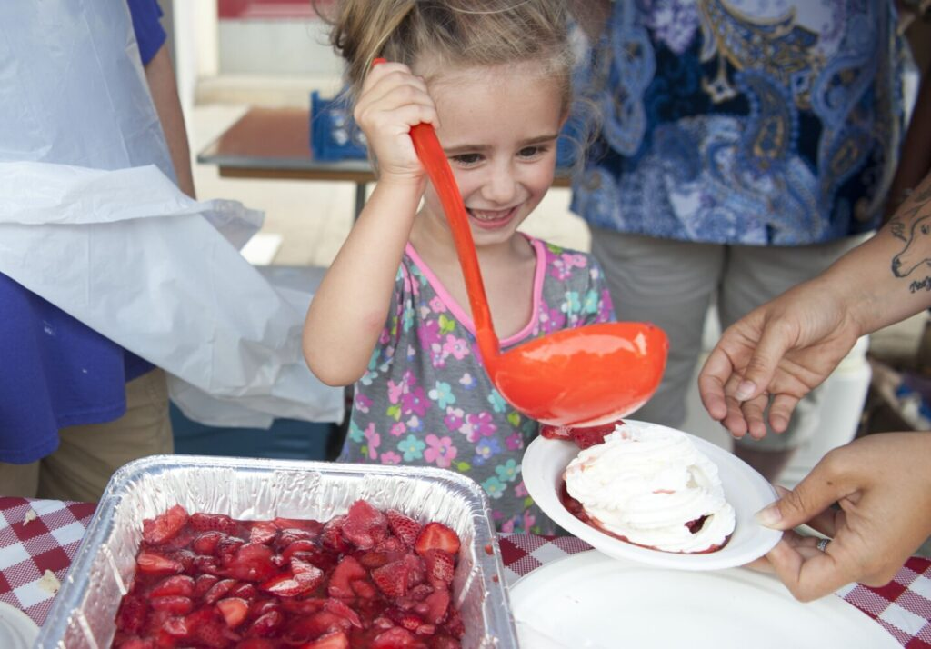 Adrea Jones, 5, ladles a helping of strawberry shortcake at the Oak Grove Center tent with the help of Erika Semones, right, at the 2019 annual Taste of Waterville on Main Street in downtown Waterville.