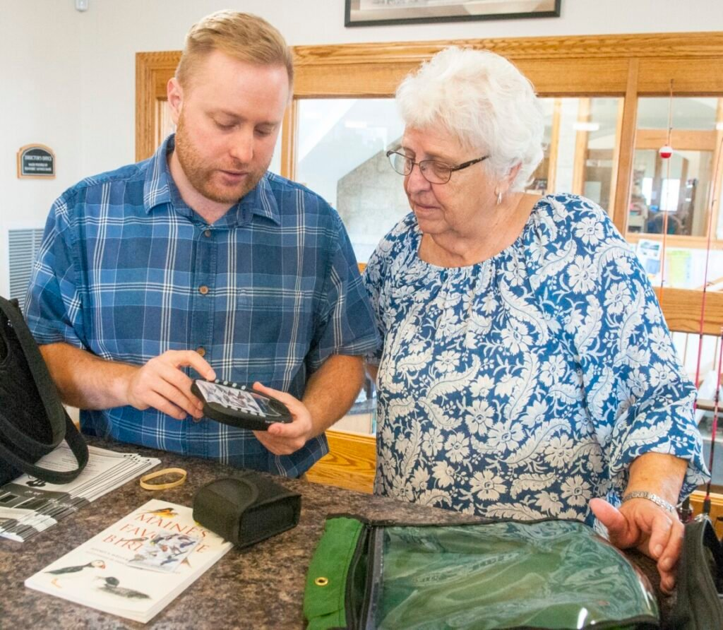 Library director Richard Fortin, left, shows Mary Jane Auns how to use the bird call identifying device that is part of the bird watching kit on Friday at Charles M. Bailey Public Library in Winthrop.