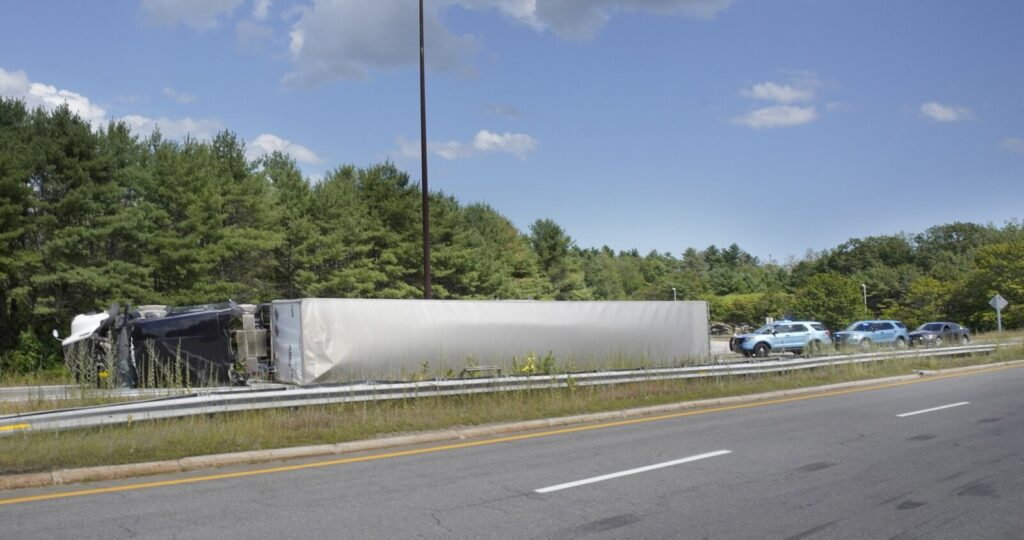 A tractor-trailer rests on its side after rolling over at the on-ramp to the Falmouth Spur of the Maine Turnpike from Interstate 295 southbound in Falmouth on Friday.