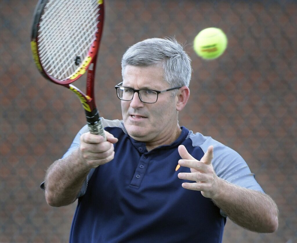 Mark Gelsinger plays tennis on Tuesday with his partner, Ken Wells, near their home in Gardiner.