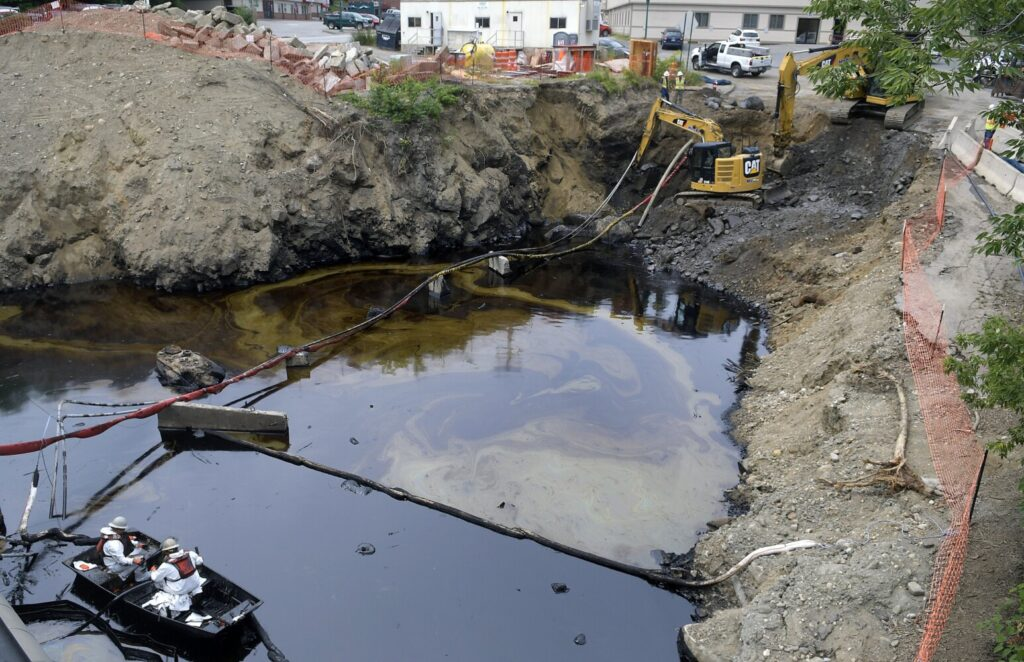 Workers clean oil Tuesday from a pit on Arcade Street in Gardiner.