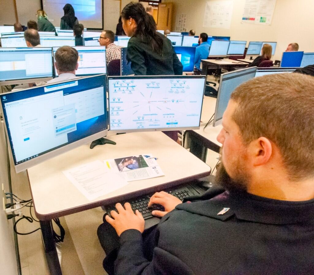 Josh Dostie, right, sits in the back row during a cyber range demonstration Friday at the University of Maine at Augusta.
