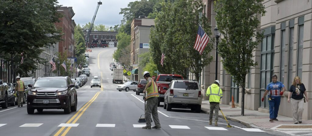 Sargent Corp. workers sweep a crosswalk Monday on Water Street in Augusta. The road opened in the morning to two-way traffic.