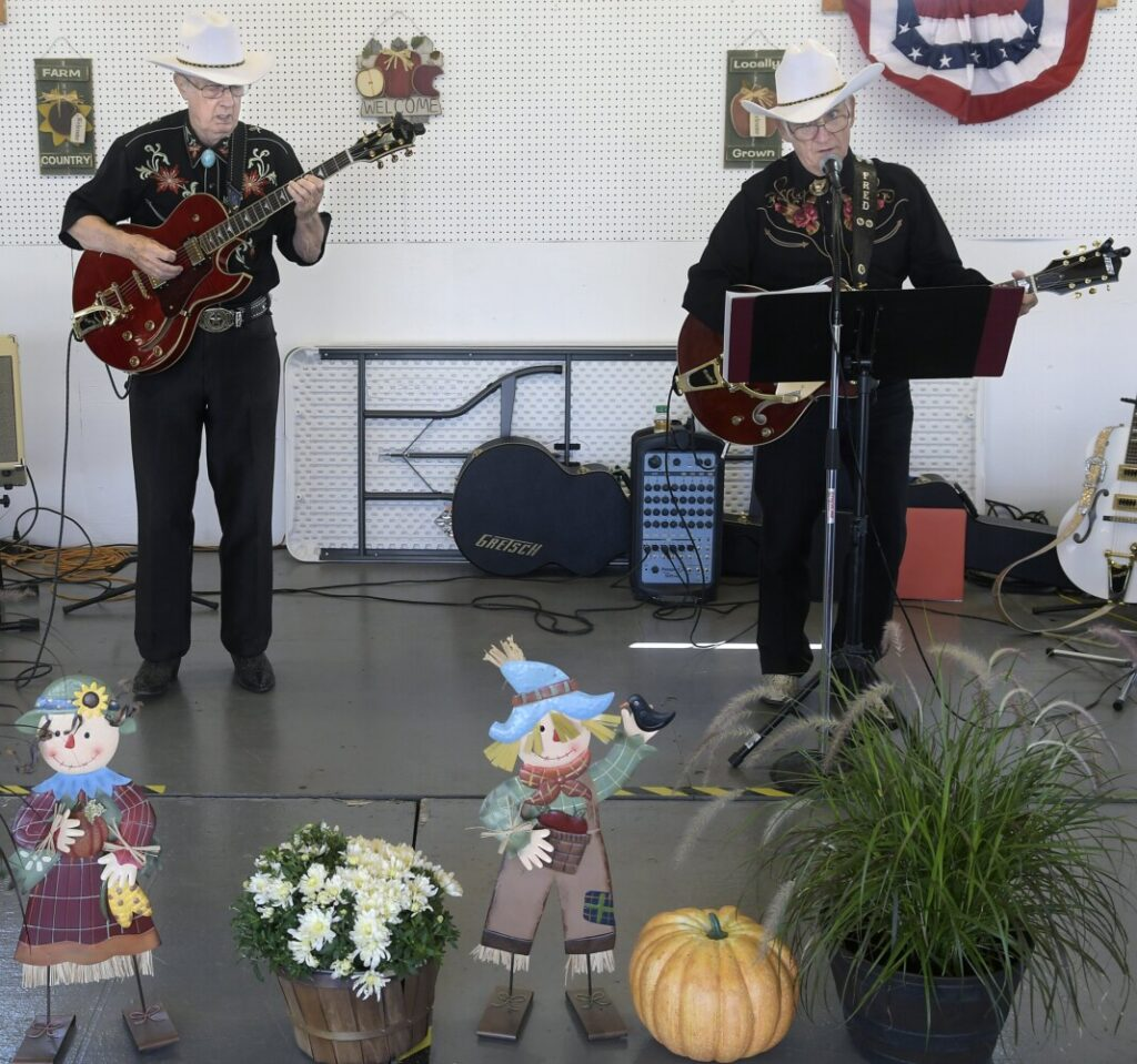 The Country Gentlemen, composed of Tom Berube, left, and Fred Couverette, serenade fair-goers Sunday on the first day of the Windsor Fair.