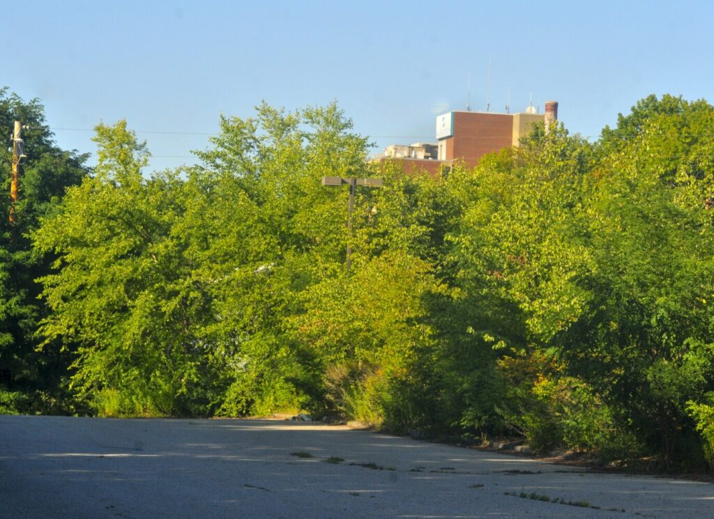 The Ballard Center in Augusta can be seen behind trees from a parking lot at the corner of Eastern and Arsenal streets on Tuesday. The lot between Kennebec Arsenal and Ballard Center is a possible site for a new Augusta Police station.