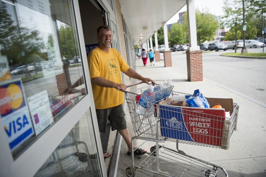 Bruce Palmer heads out of Save-A-Lot at The Concourse in downtown Waterville on Thursday with his boxed groceries.