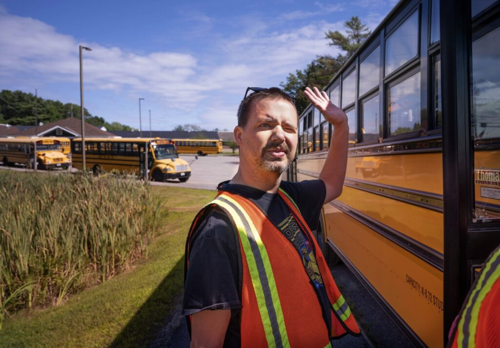 Joshua Strong waves to a passer-by while waiting for buses to leave on Wednesday at Great Salt Bay Community School in Damariscotta, where he works as a traffic guard in the afternoons.