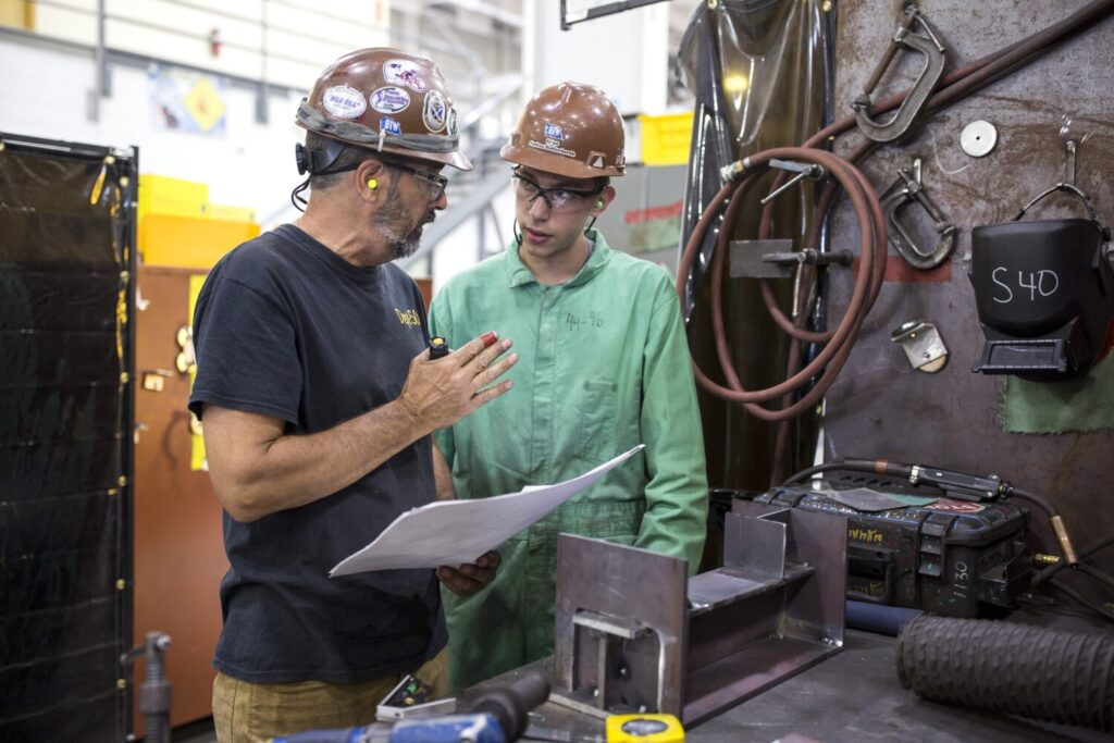 Instructor Kirk Ingalls, left, works with trainee Joshua Hofferberth at the Bath Iron Works training facility at Brunswick Landing. The push for new workers at BIW has resulted in a little over 700 trainees who have completed training in six months.
