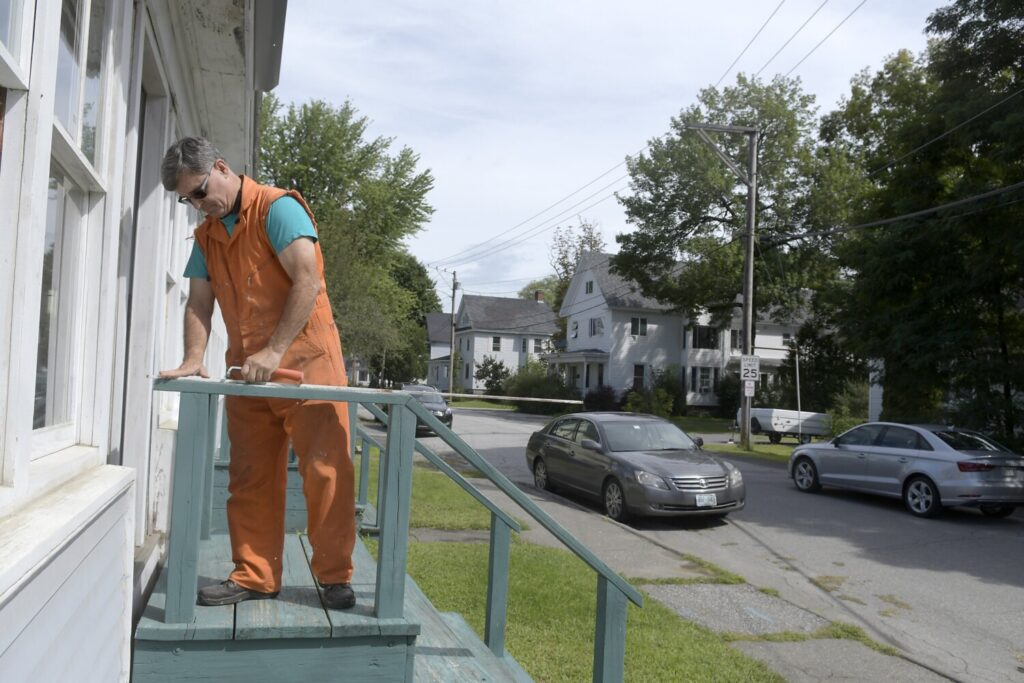 Craig Woodward replaces a window at his home Aug. 29 on Maple Street in Augusta. A 29-unit apartment complex has been built at the dead end of the street.