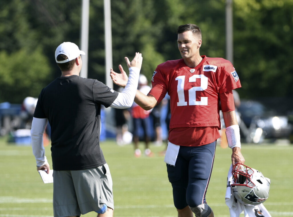 Detroit General Manager Bob Quinn, left, greets Patriots quarterback Tom Brady as the teams practiced together Monday in Allen Park, Mich.