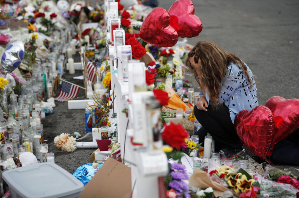 "Gloria Garces kneels at a makeshift memorial last month near the scene of a mass shooting in El Paso, Texas. The National Rifle Association called a Texas Republican's gun control proposal a ""political gambit."""