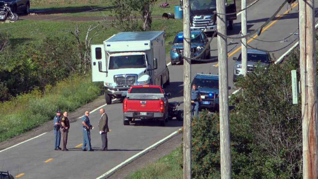 In this image from video provided by WAGM-TV, law enforcement investigators surround a red pickup truck where two people were found shot to death in Castle Hill on Tuesday. The victims were identified as Roger Ellis, 51, and Allen Curtis, 25, both of Castle Hill.