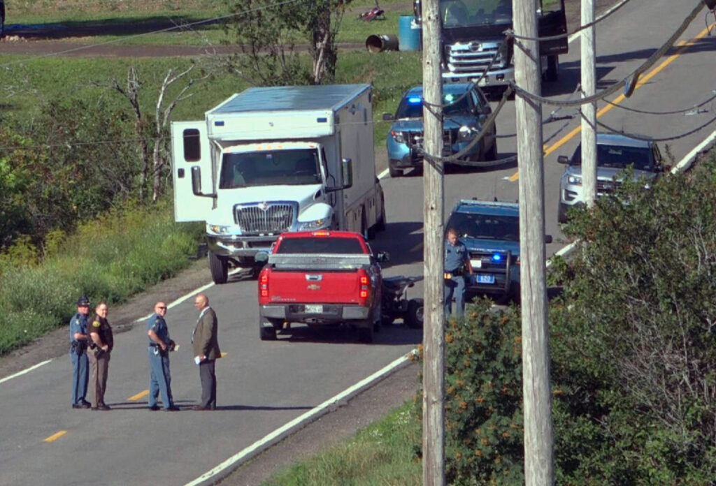 In this image from video provided by WAGM-TV, law enforcement investigators surround a red pickup truck where two people were found shot to death in Castle Hill in August. The victims were identified as Roger Ellis, 51, and Allen Curtis, 25, both of Castle Hill.