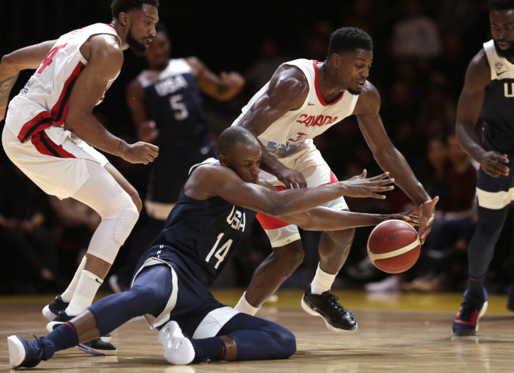 Canada's Melvin Ejim, second right, and Khris Middleton of the United States, second left, compete for the ball during the United States' 84-68 win in an exhibition game Monday in Sydney, Australia.